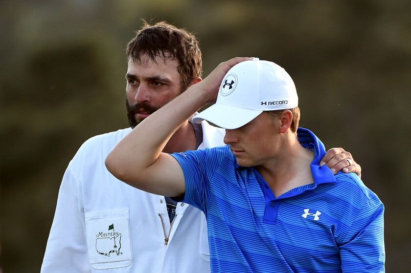 Jordan Spieth gets a pat on the back from caddie Michael Greller on the 18th hole after finishing second at the Masters.