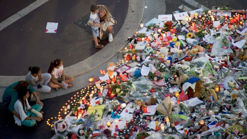 People gather at a memorial of flowers and candles on the Promenade des Anglais in Nice, France, where a truck crashed into the crowd during Bastille Day celebrations.