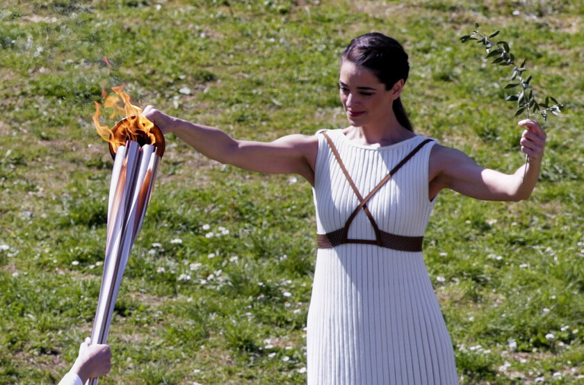 Greek actress Xanthi Georgiou, playing the role of High Priestess, passes the flame to the first torchbearer.