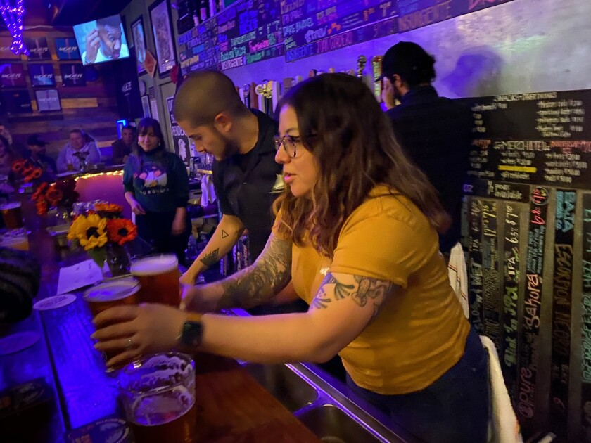 Bartender Joann Cornejo serves two craft beers at Machete Beer House in National City on Dec. 19. The establishment held an event for Insurgente, a brewery facing shut-down in Tijuana.
