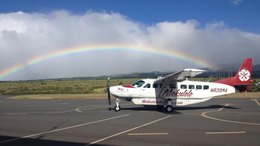 A rainbow arches near a Mokulele Airlines plane at Kapalua on the island of Maui.