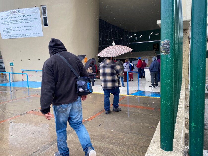 During Friday's downpour, a small crowd formed outside IMSS Clinic 20 in Tijuana as they waited to be let inside the hospital to receive medical attention. Many were wearing masks and coughing, but they are photographed from behind to protect their medical privacy.