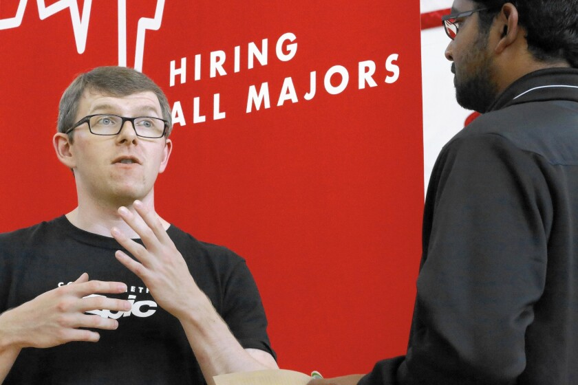 Jacob Robinson, left, of Epic, an electronic health record software company, speaks at a career fair in Illinois in September. U.S. firms are showing increased confidence in the economy.