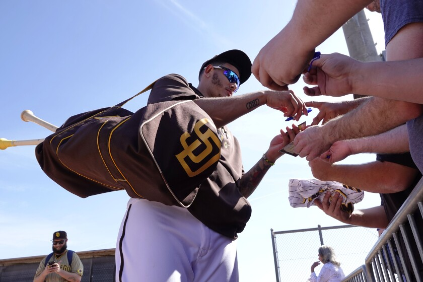 San Diego Padres Manny Machado signs autographs after spring training practice on Feb. 18.