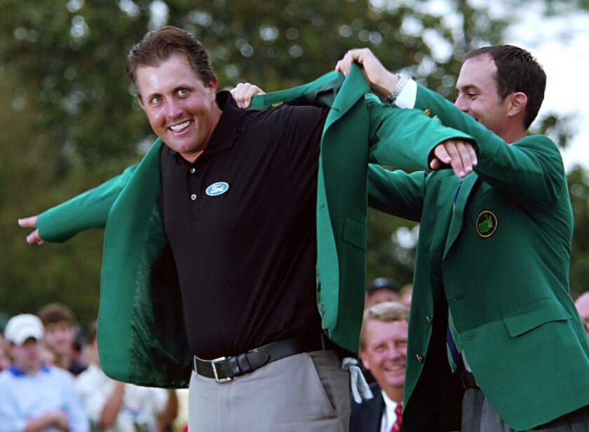 Mike Weir helps Phil Mickelson put on the iconic green jacket following Mickelson's win at the Masters in 2004.