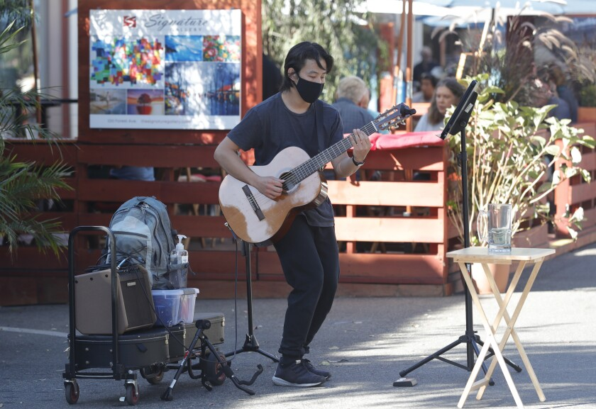 A street performer plays and sings on the Promenade on Forest in Laguna Beach in 2020.