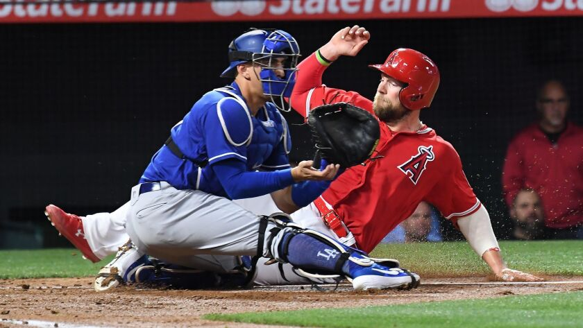 ANAHEIM, CALIFORNIA MARCH 25, 2019-Angels Kevan Smith beats the tag of Dodgers catcher Austin Barnes