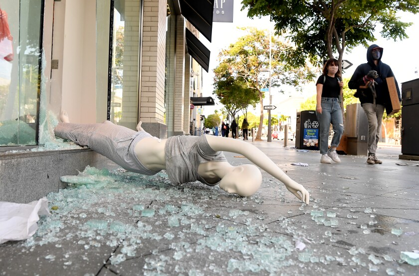 A mannequin lies on a sidewalk after businesses were vandalized Sunday in Santa Monica.