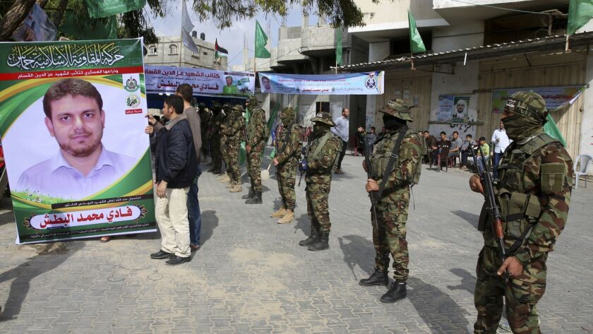 Relatives sit up a photo while masked militants from the Izzedine al-Qassam Brigades, a military win
