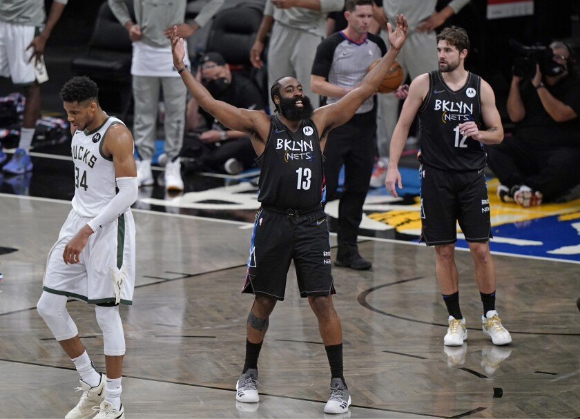 Brooklyn Nets guard James Harden (13) encourages the crowd to get behind the team during the final minutes of Game 5 of a second-round NBA basketball playoff series against the Milwaukee Bucks, Tuesday, June 15, 2021, in New York. Bucks forward Giannis Antetokounmpo (34) walks away. Nets forward Joe Harris is at right. The Nets won 114-108 to take a 3-2 lead in the series. (AP Photo/Kathy Willens)