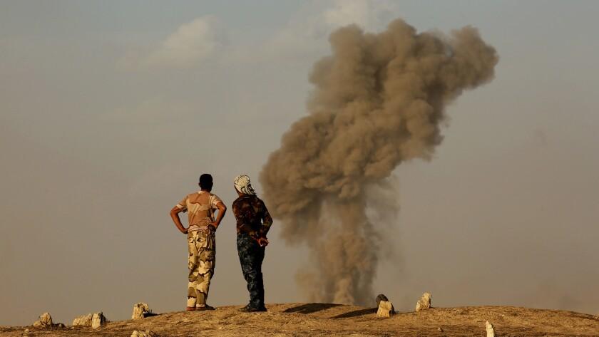 Members of Iraq's popular mobilization units watch smoke rise from a bombing near Zarqa, Iraq.
