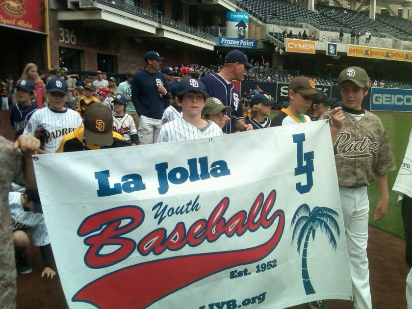 La Jolla Youth Baseball players carry their banner at PONY Day at Petco Park on Sunday. Courtesy