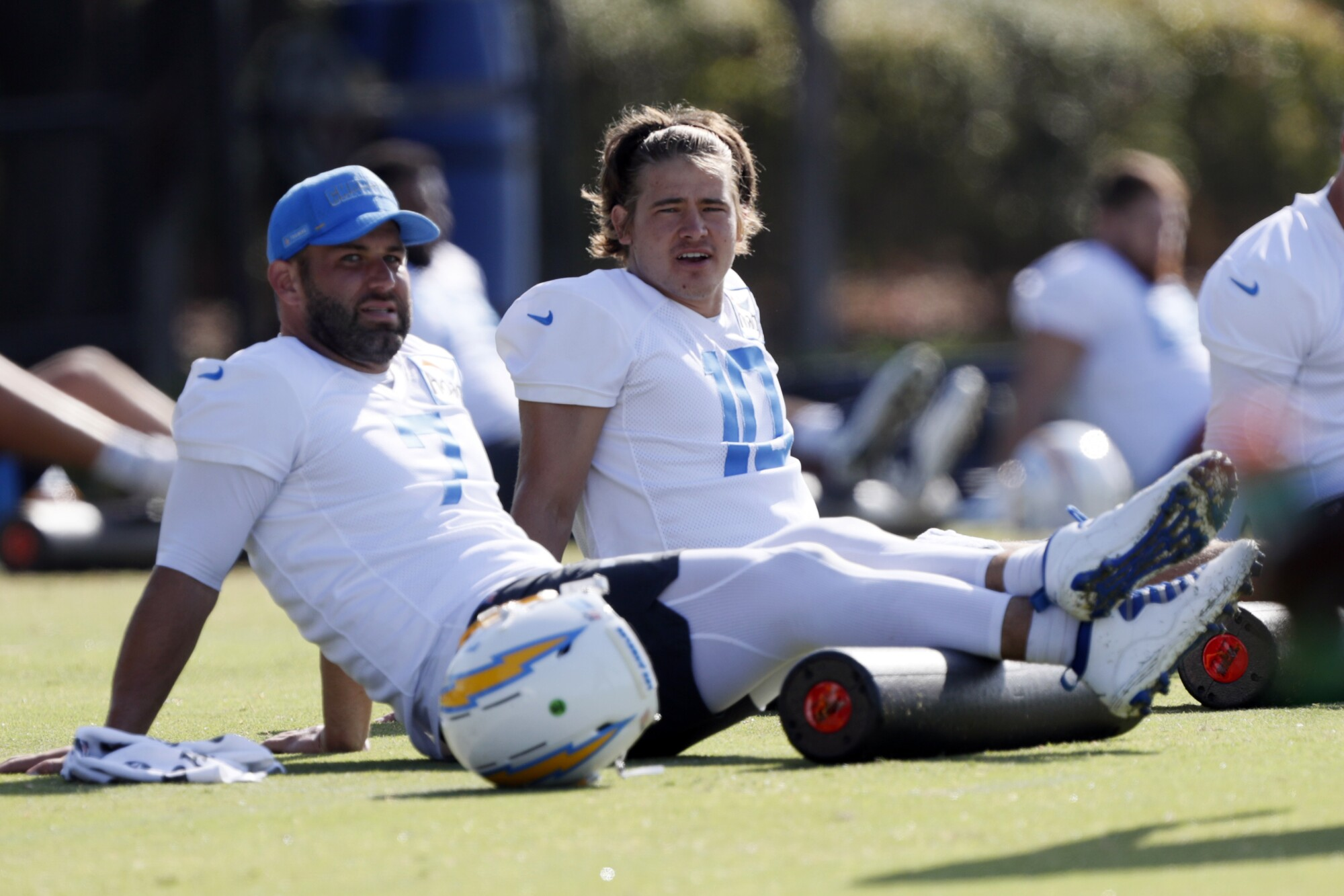 Chargers quarterback Justin Herbert talks with quarterback Chase Daniel during practice.