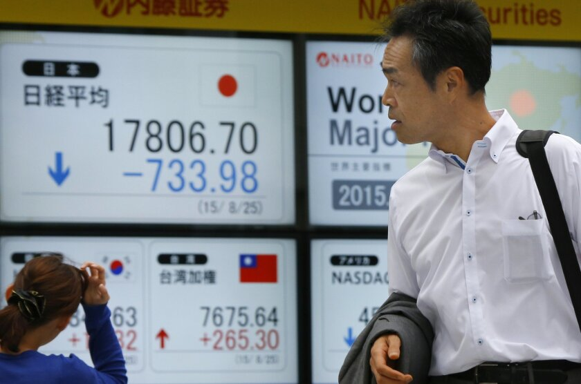 People look at an electronic stock indicator of a securities firm in Tokyo, Tuesday, Aug. 25, 2015. On Tuesday, Japan's main share index, the Nikkei 225, sank 4 percent to 17,806.70 in a session that saw the benchmark swing between positive and negative territory. It fell 4.6 percent on Monday. (AP Photo/Shizuo Kambayashi)