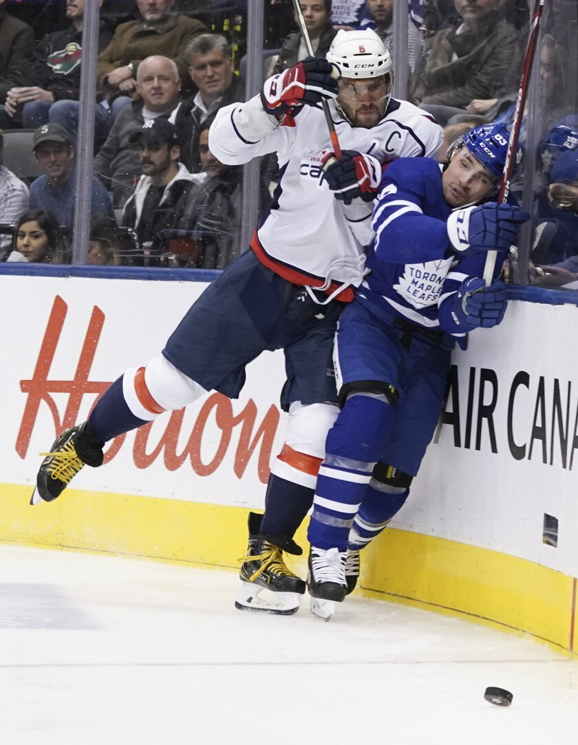 Capitals left wing Alex Ovechkin (8) checks Maple Leafs defenseman Cody Ceci (83) into the boards during a game at Scotiabank Arena.