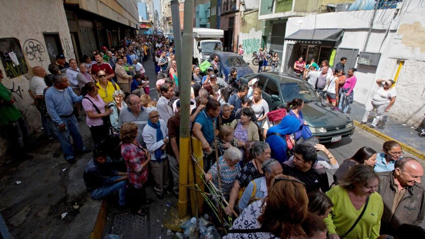 People line up outside a supermarket in Caracas, Venezuela, to buy price regulated toilet paper made