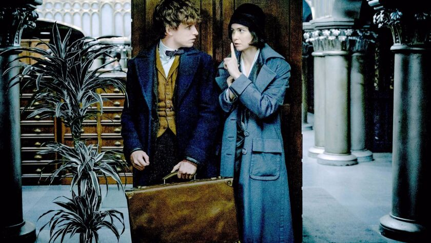 """Eddie Redmayne as Newt Scamander  -- with his signature suitcase -- and Katherine Waterston as Tina in """"Fantastic Beasts and Where to Find Them."""""""