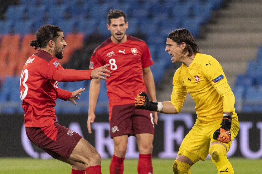 Switzerland's goalkeeper Yann Sommer, right, celebrates with Ricardo Rodriguez, left, and Remo Freuler, after stopping a penalty, during the UEFA Nations League soccer match between Switzerland and Spain at the St. Jakob-Park stadium in Basel, Switzerland, Saturday Nov. 14, 2020. (Alessandro della Valle/Keystone via AP)