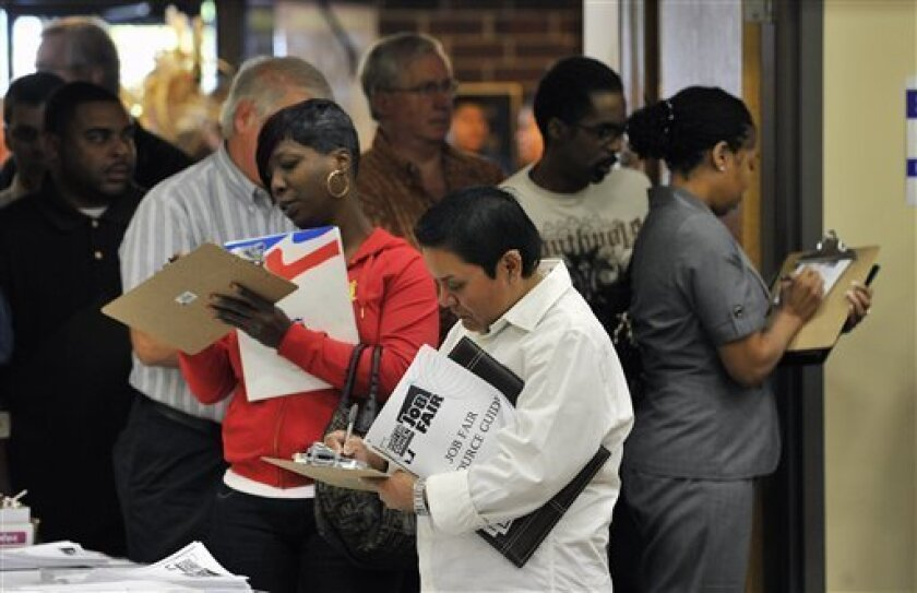 Unemployed workers fill out applications during a jobs fair sponsored by Scott Lee Cohen, Independent Candidate for Governor of Illinois on Tuesday, Oct. 5, 2010, in Rockford, Ill. Americans are borrowing and spending less as they face widespread unemployment and uncertainty about their financial futures. The reduced use of credit by consumers is a drag on the recovery, which has yet to show a sustained rebound. (AP Photo/Jim Prisching)