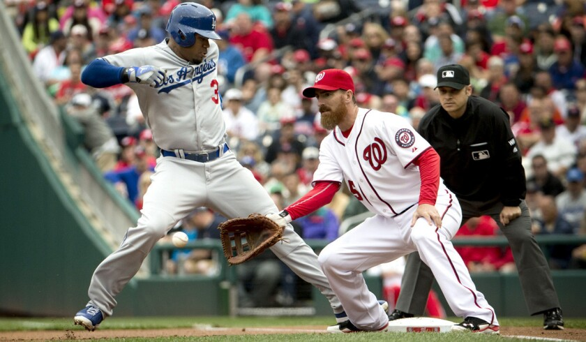 Dodgers left fielder Carl Crawford (3) gets back to first base before Washington's Adam LaRoche can make the catch and tag in the game Wednesday.