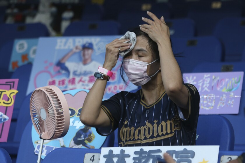 FILE - In this May 8, 2020, file photo, a fan tries to cool off at Xinzhuang Baseball Stadium in New Taipei City, Taiwan. The Taiwan baseball league is continuing as a trailblazer for sports resuming after the lockdown in the coronavirus pandemic. An easing of restrictions by the government on Sunday, June 7, 2020 allows more fans at the ballparks and allows them to sit closer together while they're supporting their teams in the Taiwan-based CPBL. Fans are only required to wear face masks when they're not in their seats and ball parks are allowed to be up to 50% capacity. (AP Photo/Chiang Ying-ying, File)