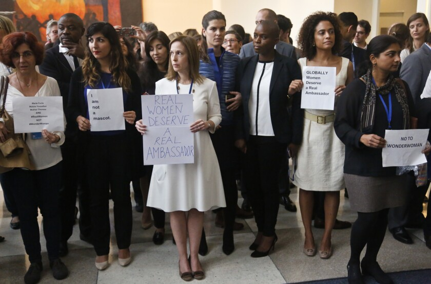 United Nations staff, some holding signs, stand in a silent protest against naming Wonder Woman a U.N. ambassador.