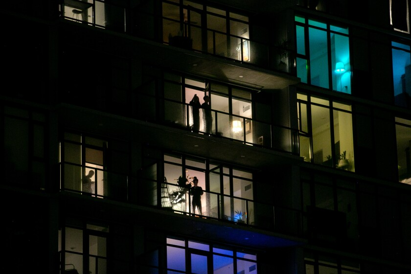 Residents cheer on healthcare workers from their balconies at the Alexan ALX apartments in the East Village neighborhood of downtown San Diego on April 6, 202,0 in San Diego.
