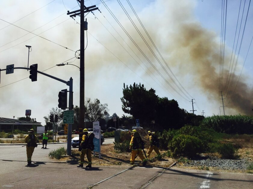 Smoke billows from brush off E Street and Bay Boulevard in Chula Vista Tuesday as firefighters prepare to pack hoses to the fire.