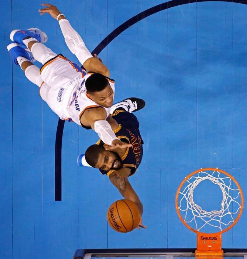 Kyrie Irving (d) de los Cavaliers lanza contra Russell Westbrook (i) de Thunder durante un partido. EFE/Archivo