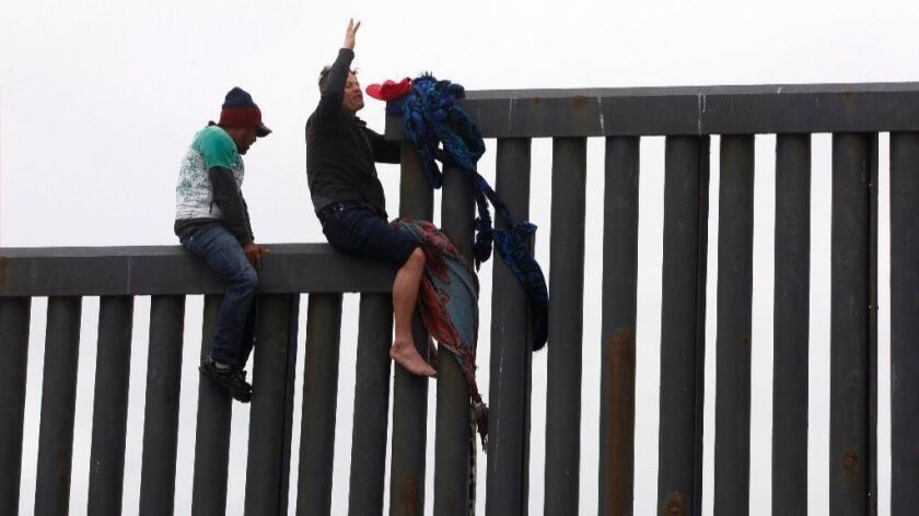 TIJUANA, March 21, 2019 | Minutes before he drops down on the U.S. side of the U.S. - Mexican border barrier, with Border Patrol agents waiting, a Honduran migrant raises up his arm at Playas de Tijuana, Mexico on Thursday. | Photo by Hayne Palmour IV/San Diego