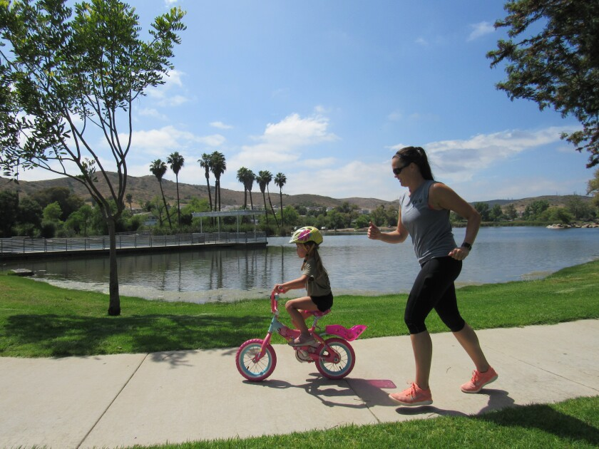 Lauren Green keeps up with her daughter, Rosie, who was learning to ride a bicycle at Santee Lakes.