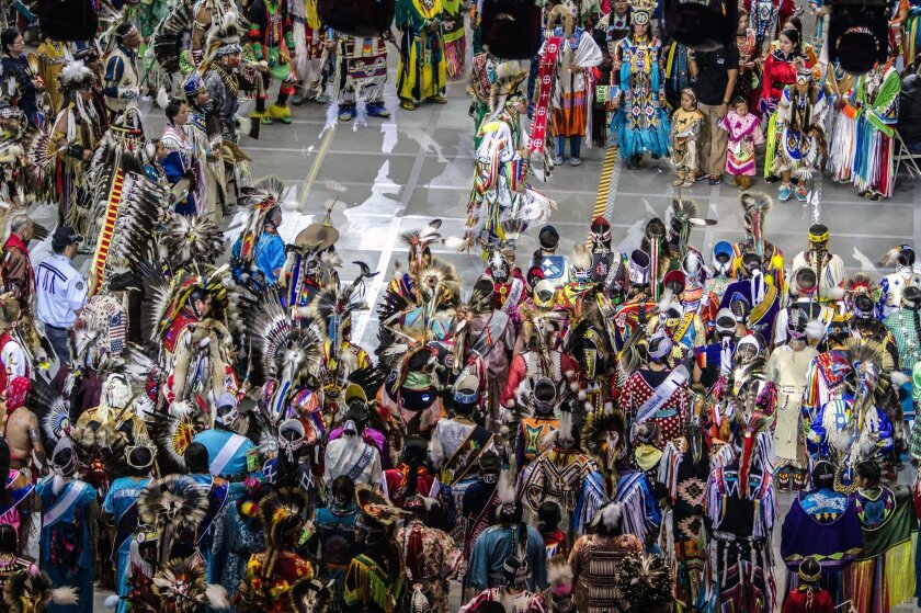 FILE - In this April 25, 2015, file photo, Native American and indigenous dancers surround head man dancer, Juaquin Hamilton, from Shawnee, Okla., following the grand entrance of the annual Gathering of Nations in Albuquerque N.M. One of North America's largest powwows has announced Wednesday, June