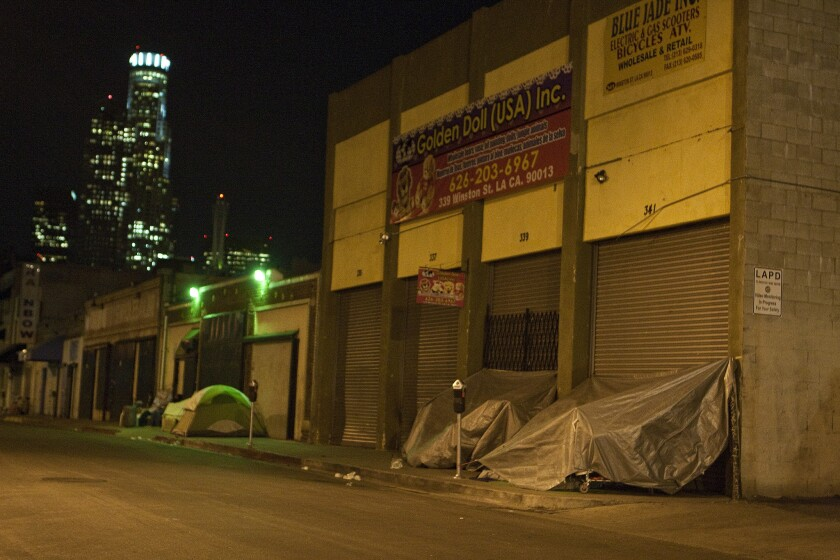 Homeless people prepare their tents and tarps for shelter on Winston Street near San Pedro Street in the Skid Row area of downtown Los Angeles.