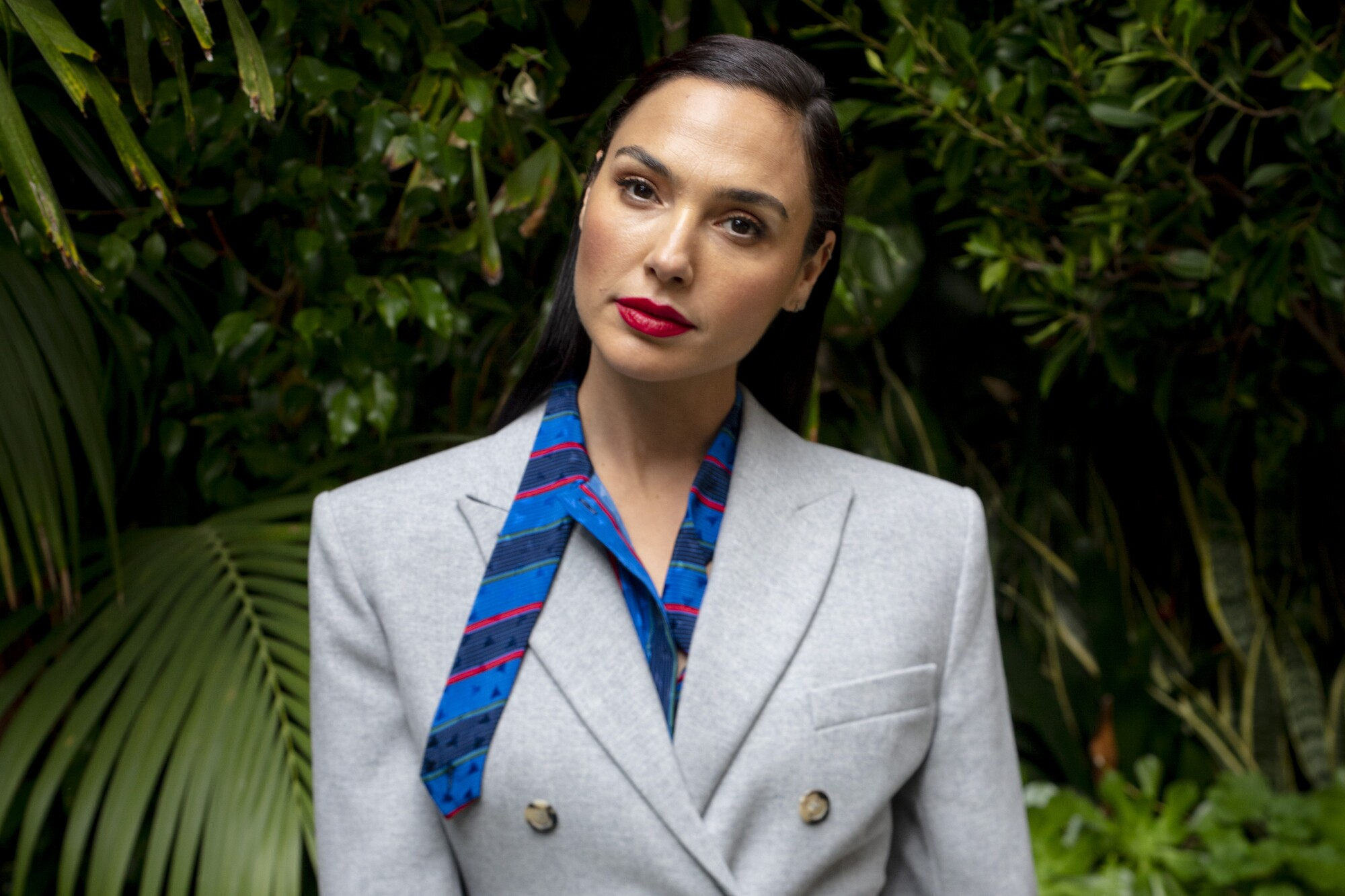Gal Gadot stands for a portrait in front of greenery.