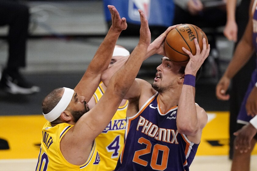 Phoenix Suns forward Dario Saric, right, shoots as Los Angeles Lakers forward Jared Dudley defends during the first half of an NBA basketball game Tuesday, March 2, 2021, in Los Angeles. (AP Photo/Mark J. Terrill)