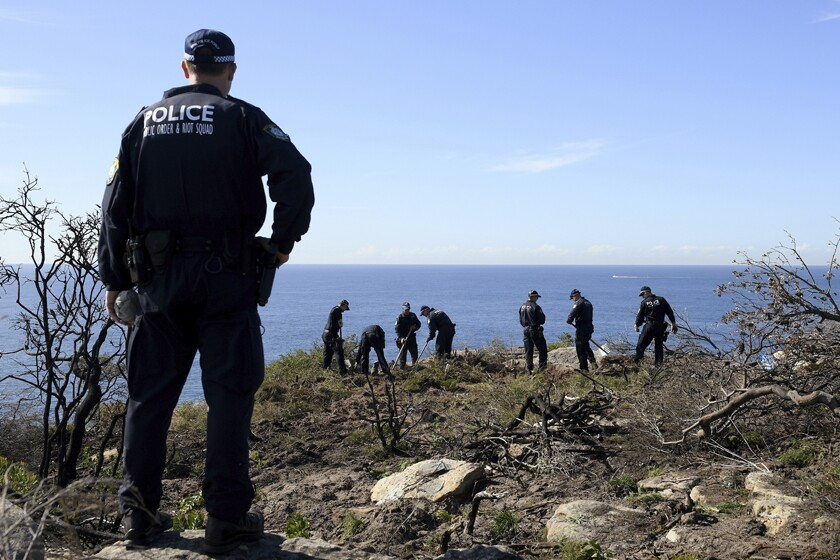 Police search a headland May 12 in Sydney following an arrest tied to the death of American Scott Johnson in 1988.