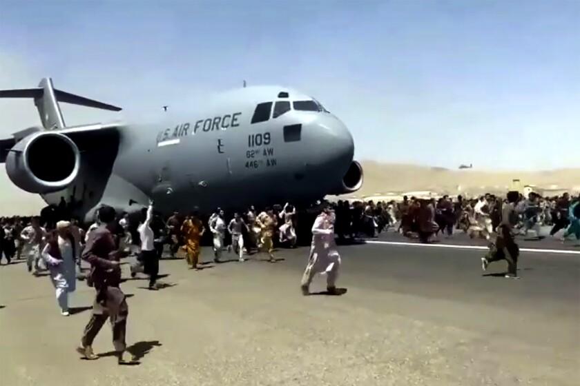 Hundreds of people run alongside a U.S. Air Force C-17 transport plane