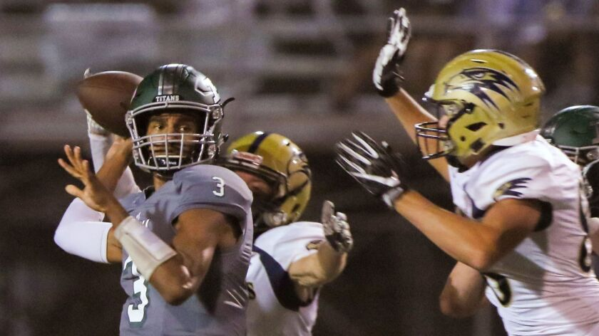 Poway quarterback Maximus Brown is pressured by Del Norte's Evan Goldstein (right) and Jahmal Clarke (from behind). With Poway leading 20-0, the game was called in the first quarter because of lightning.