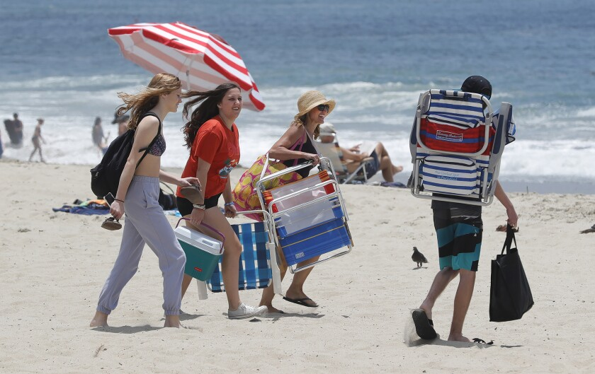 Beachgoers walk across the sand looking for a spot to post their chairs on a warm afternoon in Laguna Beach on Tuesday.