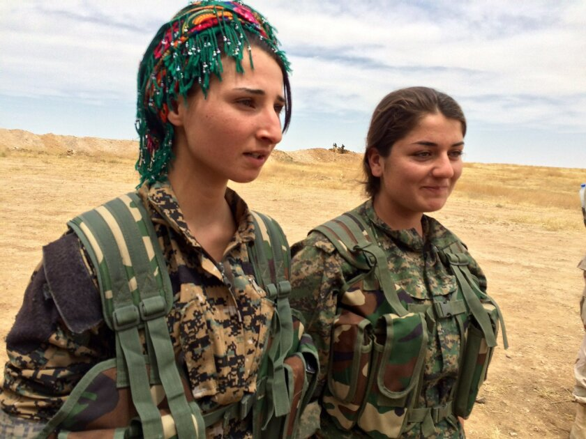 """In this photo taken May 21, 2016, Barcham Zana, left, and Helene Osman, at a training camp in northern Syria where US military advisers are working with local Arab volunteers who want to fight the Islamic State. At age 20, Zana knows her enemy. It is the Islamic State, which she calls """"darkness."""" Two cousins were killed by IS, she said, so for her this is not an abstract threat. (AP Photo/Robert Burns)"""