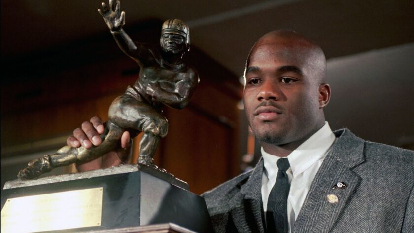 In this Dec. 10, 1994, file photo, Colorado's Rashaan Salaam poses with his Heisman Trophy at the Downtown Athletic Club in New York.