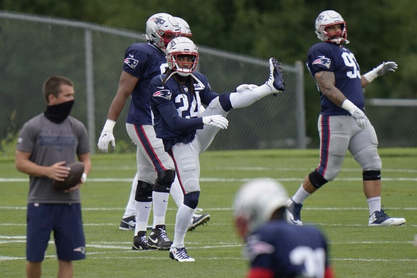 New England Patriots cornerback Stephon Gilmore (24) stretches during an NFL football training camp practice, Monday, Aug. 17, 2020, in Foxborough, Mass. (AP Photo/Steven Senne, Pool)