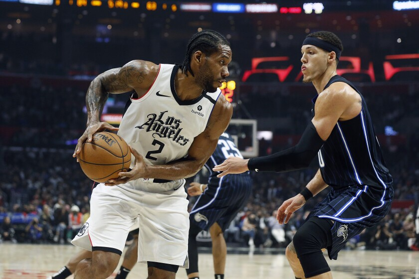 Kawhi Leonard looks to make a move against Magic forward Aaron Gordon during the second half of a game Jan. 16 at Staples Center.