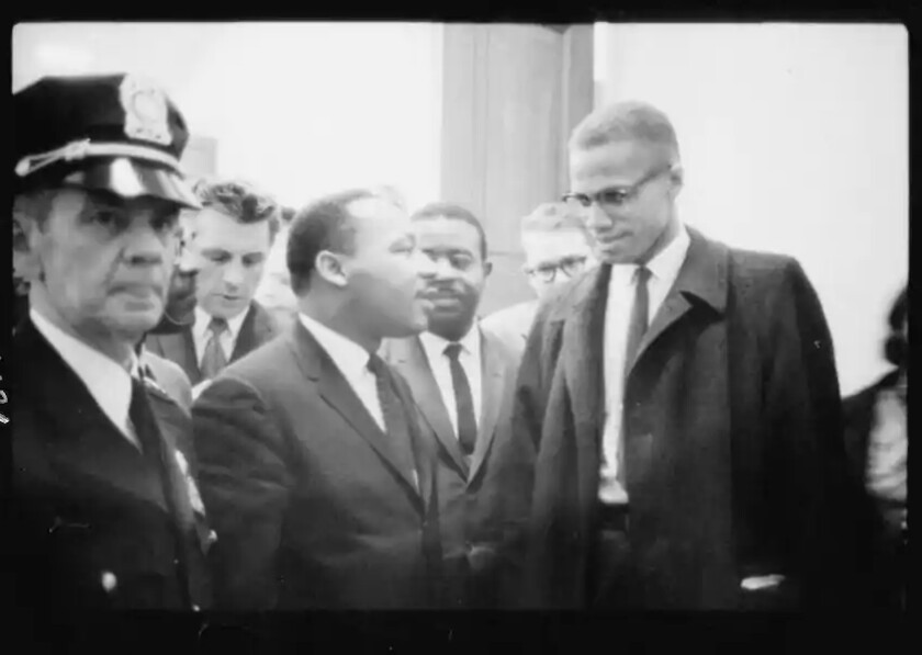 A photograph of Martin Luther King Jr., center, and Malcolm X, right, taken in 1964 in Washington, D.C.
