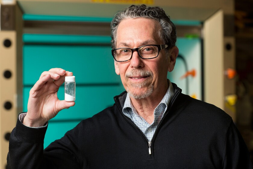 The Salk Institute's Dr. Ronald Evans, director of the Gene expression Laboratory, holds a vial of fexaramine.