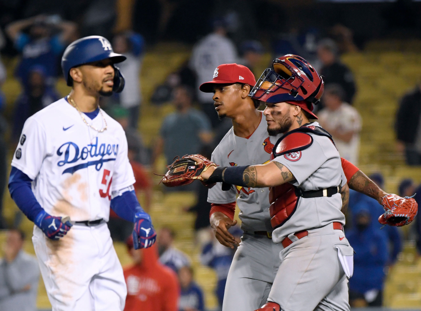The Dodgers' Mookie Betts heads to the dugout as the Cardinals' Alex Reyes (29) and Yadier Molina (4) celebrate a  win.