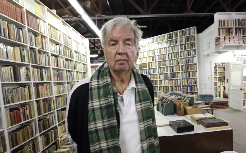 Larry McMurtry stands in front of shelves stacked with books,