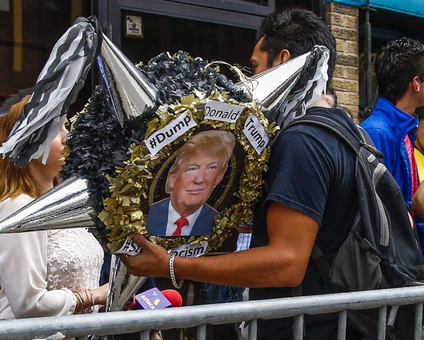 Un hombre de la comunidad mexicana protesta afuera del restaurante donde el empresario y candidato a la presidencia de los Estados Unidos por el partido Republicano Donald Trump (no en la foto) hablo ante ciudadanos hoy, lunes 29 de junio de 2015, en Chicago (EE.UU.). Trump ha sido acusado de ser un racista por los comentarios que hizo al anunciar su candidatura presidencial. Donald Trump dijo ante una multitud de 350 empresarios y líderes cívicos que el es el único que puede volver a hacer fuerte y grande a EEUU otra vez.