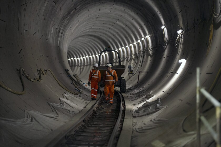 FILE - In this Wednesday, April 22, 2015 file photo, people walk along a Crossrail tunnel that heads off in a north easterly direction towards Stratford from the Stepney Green shaft in east London. The planned opening of London's new east-west railway, Crossrail, was delayed again Friday, Nov. 8, 2019 as costs increased by up to 650 million pounds ($832 million). The 73-mile (118-kilometer) line, which will be formally known as the Elizabeth Line - after Queen Elizabeth II - is Britain's biggest infrastructure project in decades. (AP Photo/Matt Dunham, file)