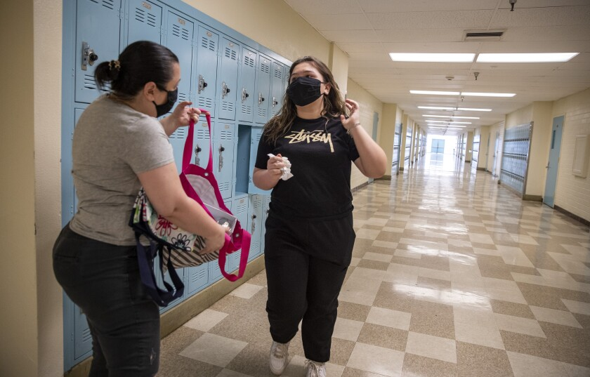 Jamie Zamudio, left, helps her daughter Isabella, 14, clean out her locker at El Camino Real Charter High School on April 30.